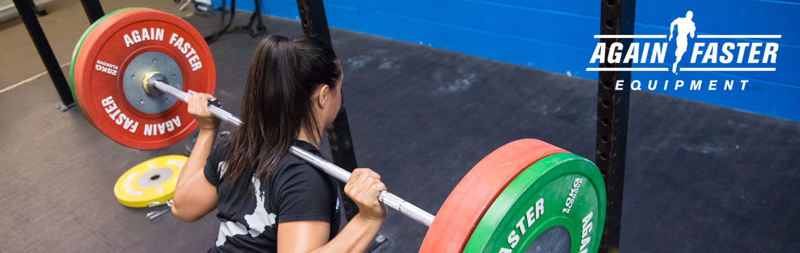 Tracey Stewart back squating with Again Faster Barbell and Weights Banner